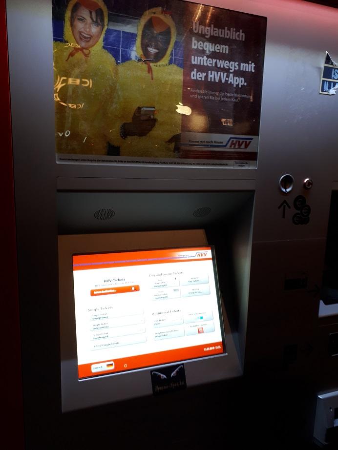 Автомат по продаже билетов. На нем видна реклама приложения HVV App, позволяющего отслеживать транспорт и планировать поездки